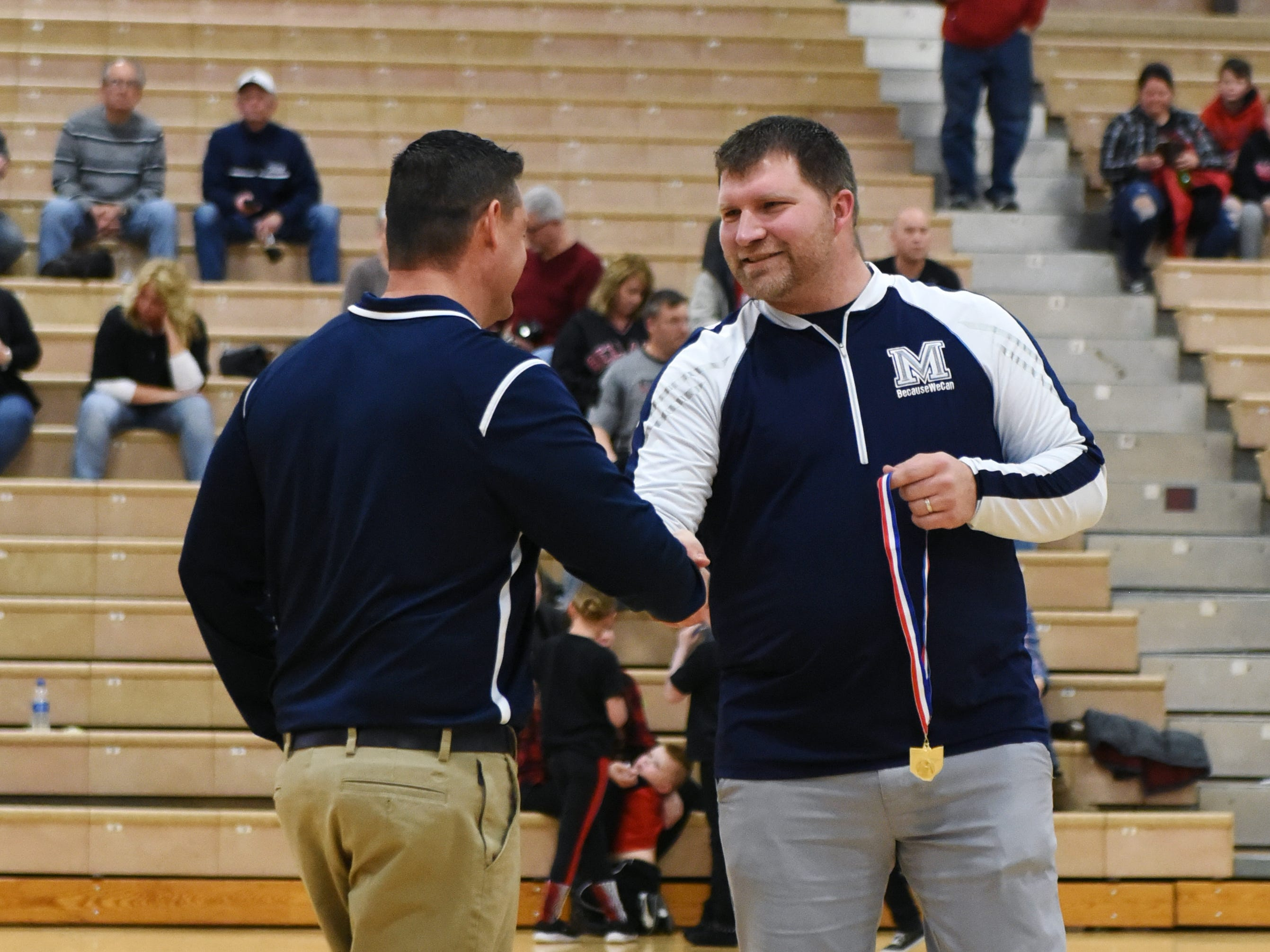 Morgan coach Matt Zumbro gets a handshake from his former player, Raiders atheltic director Adam Copeland, following Morgan's 46-44 district final win against Bellaire on Saturday. It was the Raiders' first district title in school history.