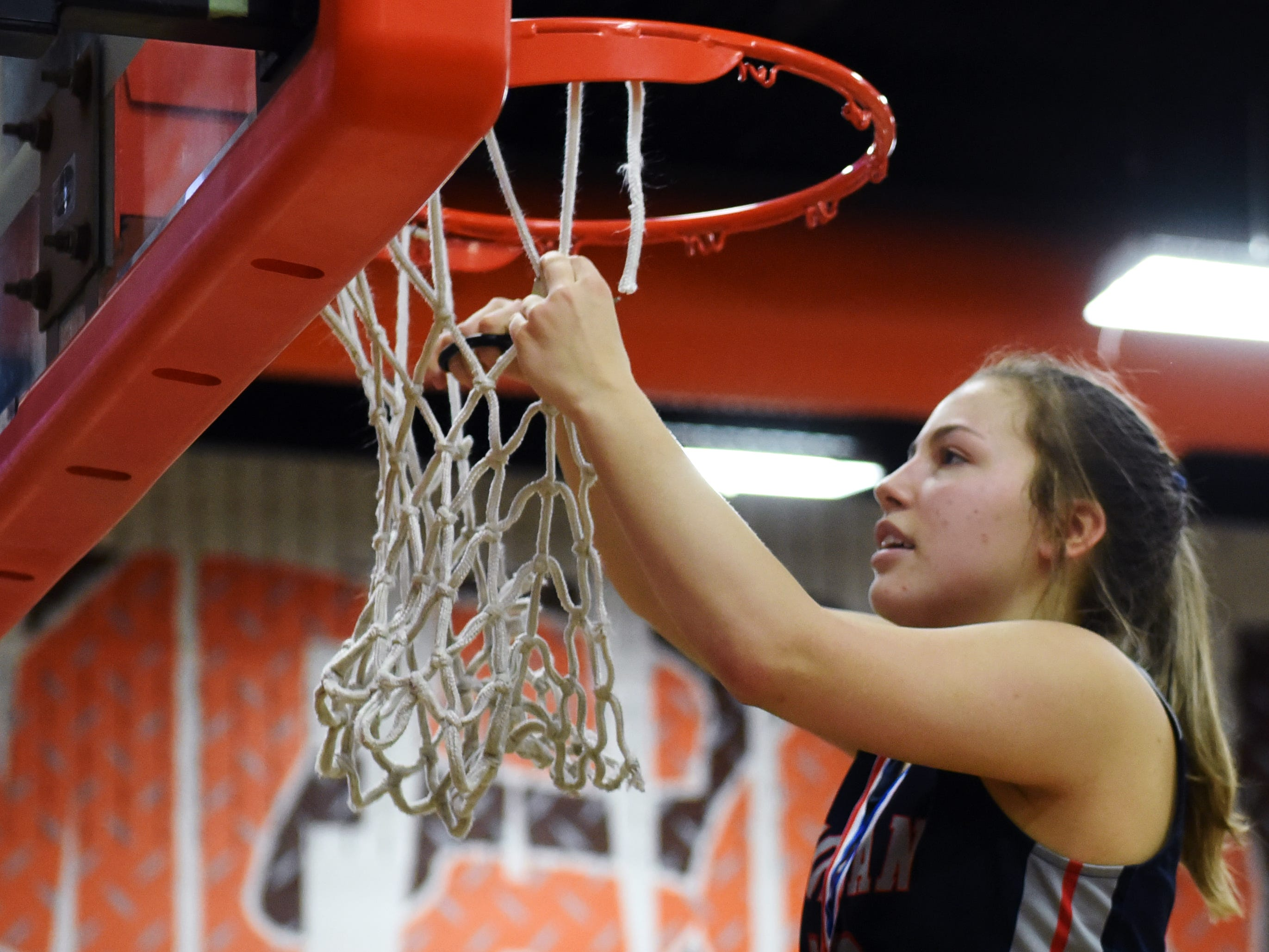 Morgan's Riley Coon cuts down the net following a 46-44 win against Bellaire in a Division III district final at Meadowbrook. Conn's 12 points shared the team lead in the game.