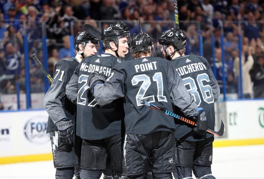 5bfd2b3ac89 Tampa Bay Lightning defenseman Ryan McDonagh (27) is congratulated by  teammates after his first
