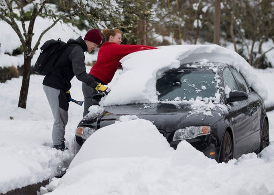 University of Oregon students Trent Ward and Mollie Herron work to clear snow from Ward's car parked in Eugene, Ore.