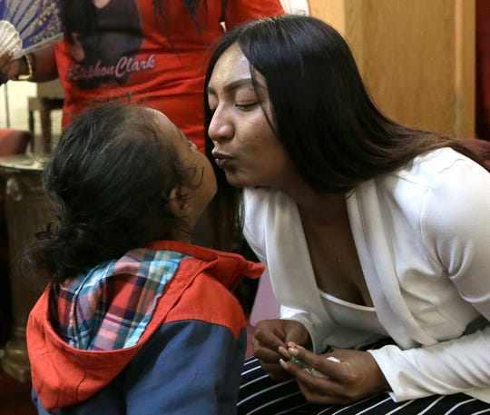 Salena Manni, the fiancee of Stephon Clark, who was shot and killed by Sacramento police in 2018, kisses the couple's youngest son, Cairo, 2, during a news conference to discuss the decision to not file charges against the two officers involved on March 2, 2019.