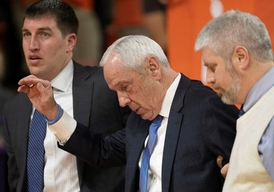 North Carolina coach Roy Williams is escorted off the court and waves, after falling near the bench during the first half.