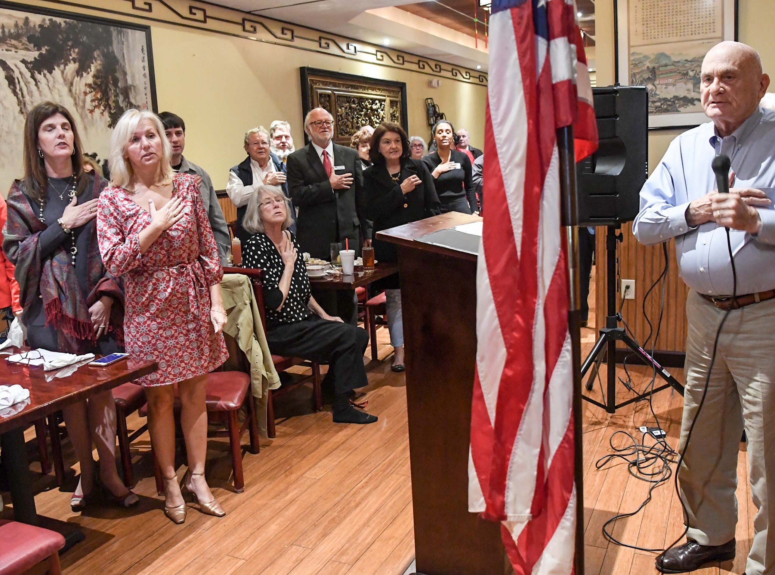 State Lt. Gov. Pamela Evette, left, joins in the Pledge of Allegiance by Bob Martin, right, of Anderson at the 1st Monday Club at Master's Wok in Anderson Monday.