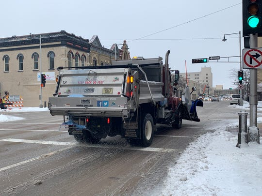 A plow drops salt on College Avenue in Appleton.