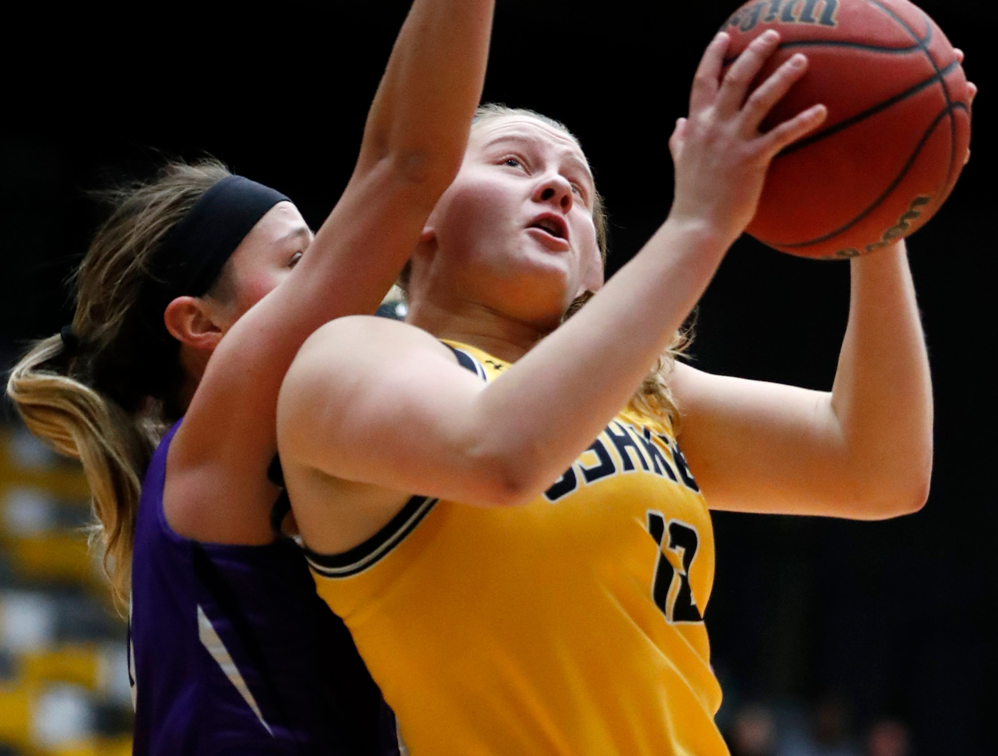 UW-OshkoshÕs Leah Porath (12) tries to push past UW-WhitewaterÕs Camri Conley (10) toward the basket during the WIAC Championship final Sunday, Feb. 24, 2019, at the Kolf Sports Center in Oshkosh, Wis.