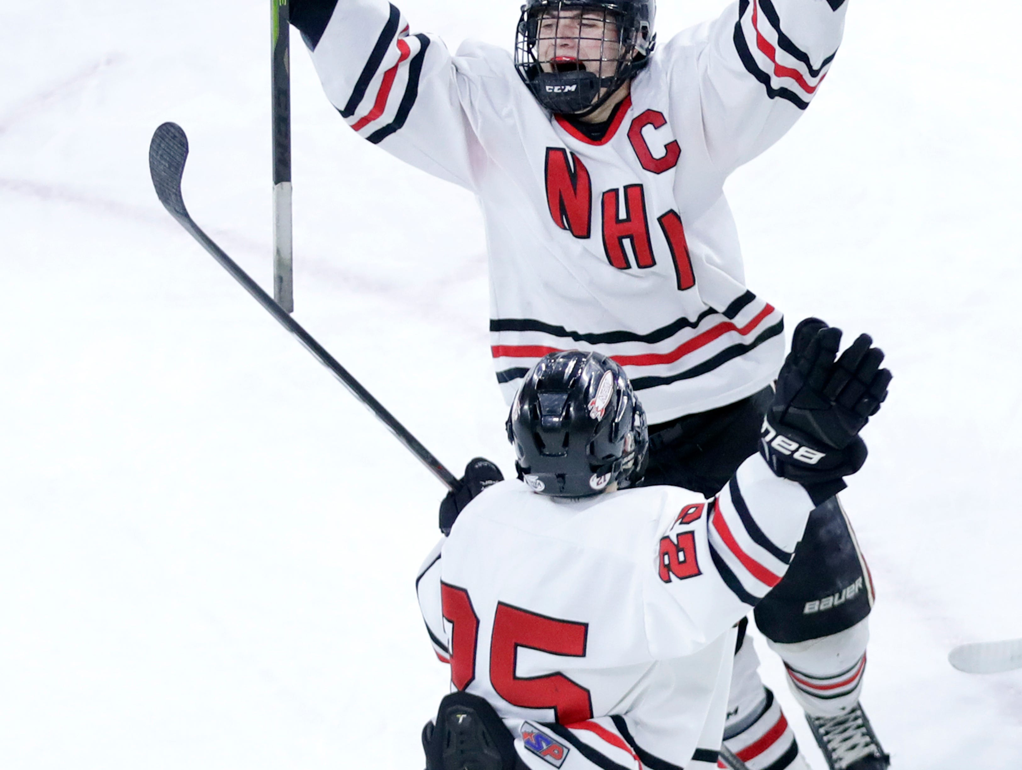 Neenah/Hortonville/MenashaÕs Dillion Fox celebrates with Neenah/Hortonville/MenashaÕs Drew Sutton after scoring a goal against Hudson Thursday, Feb. 28, 2019, at Veterans Memorial Coliseum in Madison, Wis.