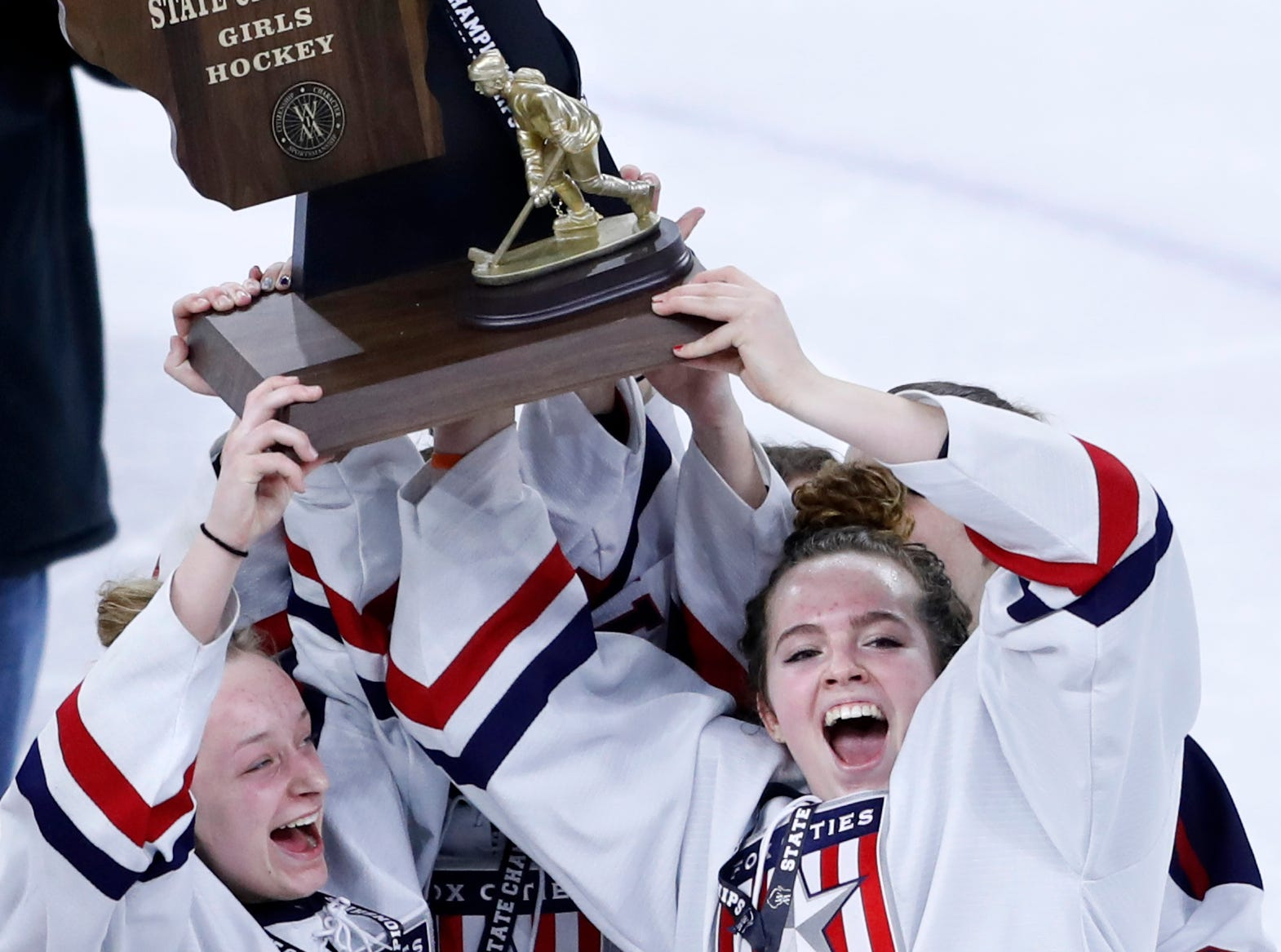 Fox Cities StarsÕ Lauryn Hull and Tori Nelson hold up the first place trophy with teammates after defeating Hudson in double overtime during the WIAA State Hockey Tournament championship match Saturday, March 2, 2019, at Veterans Memorial Coliseum in Madison, Wis.