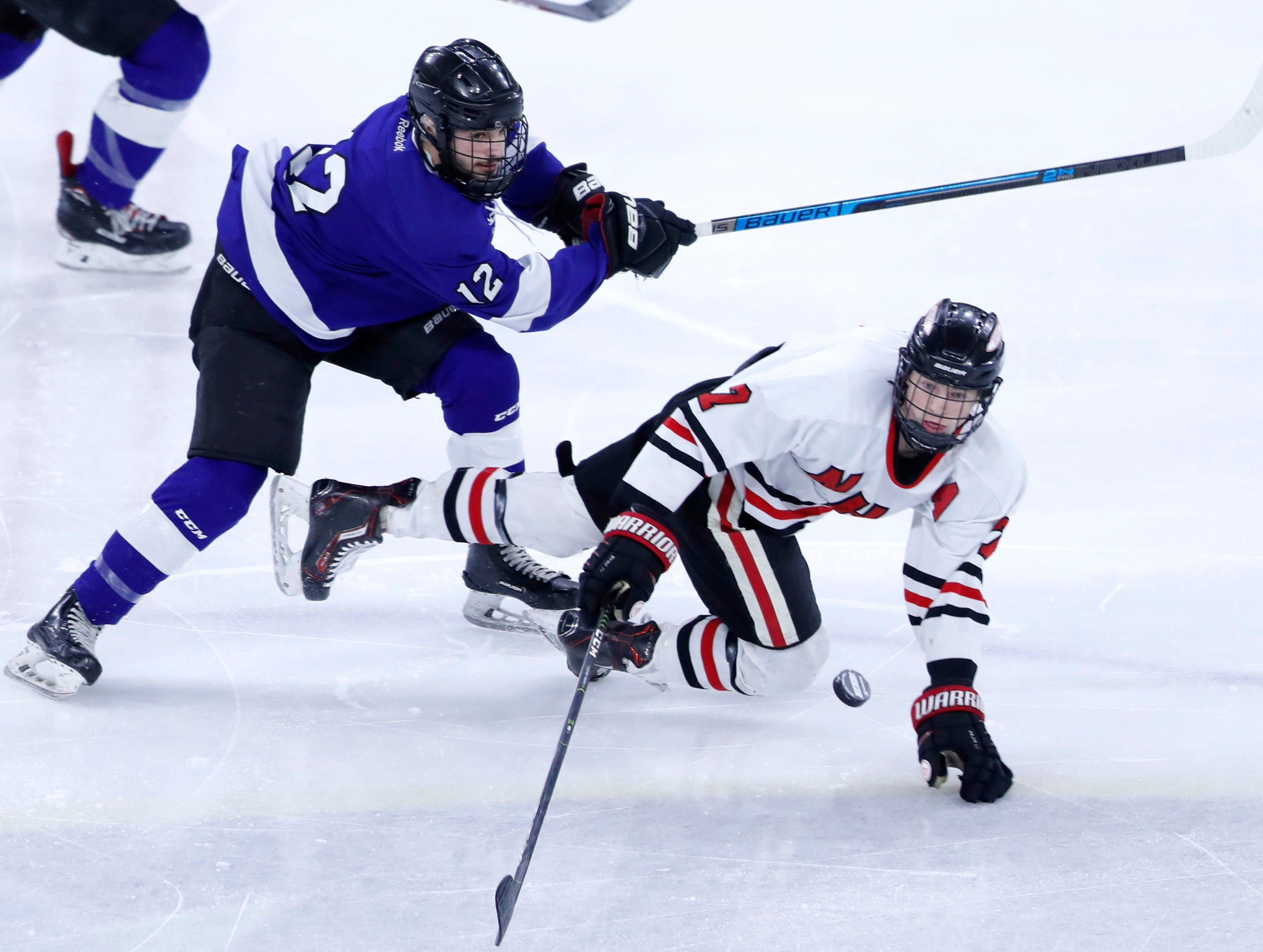 Waukesha North Co-opÕs Trenton Tucker trips up Neenah/Hortonville/MenashaÕs Ethan Long during the WIAA State Hockey Tournament semifinals Friday, March 1, 2019, at Veterans Memorial Coliseum in Madison, Wis.