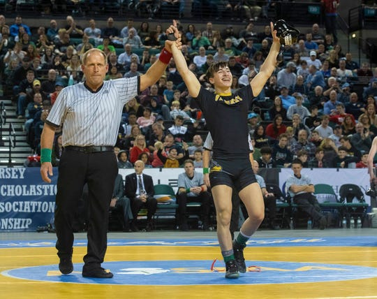 St. John Vianney's Dean Peterson has has hands raised by referee Ed Tonnessen after he won the NJSIAA 113-pound championship.