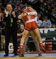 Wall's Robert Kanniard jumps into the arms of Crimson Knights' assistant coach Drew Reca while Wall head coach Brian Fischer (left) applauds after Kanniard won the NJSIAA 160-pound championship.