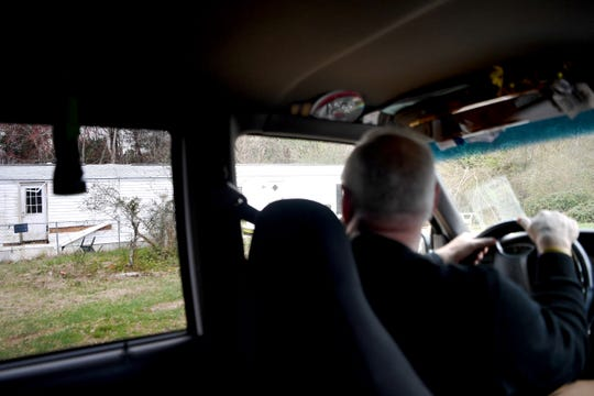 Joe Yelton, senior pastor of Hominy Baptist Church, looks from his truck at a Candler trailer home where he said a member of his congregation was found dead of a drug overdose in January.