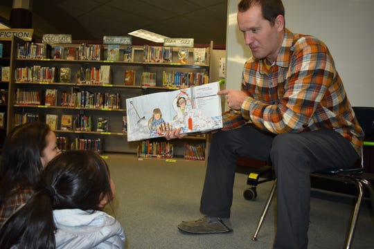 Paul Henderson, librarian at Silver Ridge Elementary in the Central Kitsap School District, reads to a class of students.