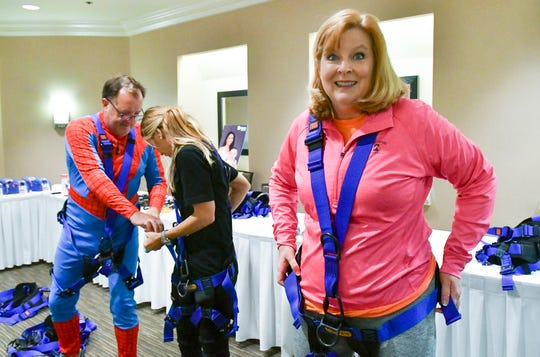Suzy Fleming Leonard prepares to go Over the Edge, rappelling off the side of the Melbourne Hilton Rialto Place during a fund raiser for Habitat for Humanity of Brevard.