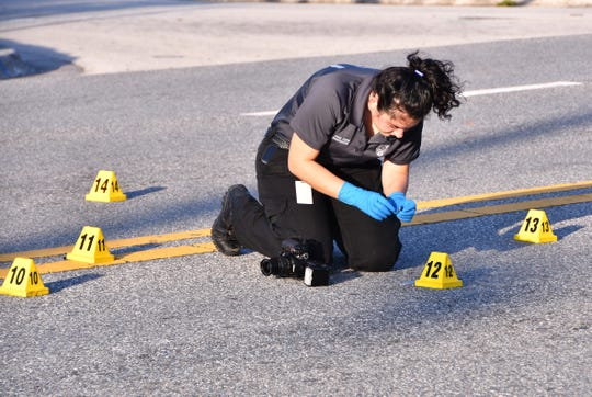 A Melbourne crime scene technician takes photos and measurements of shell casings laying in Universituy Blvd. Melbourne police said two adults were shot and wounded Monday afternoon in a drive-by shooting involving two cars near Stone Middle School on University Blvd. Police believe that an occupant of one car fired multiple shots into the occupants of another vehicle just east of the school campus.