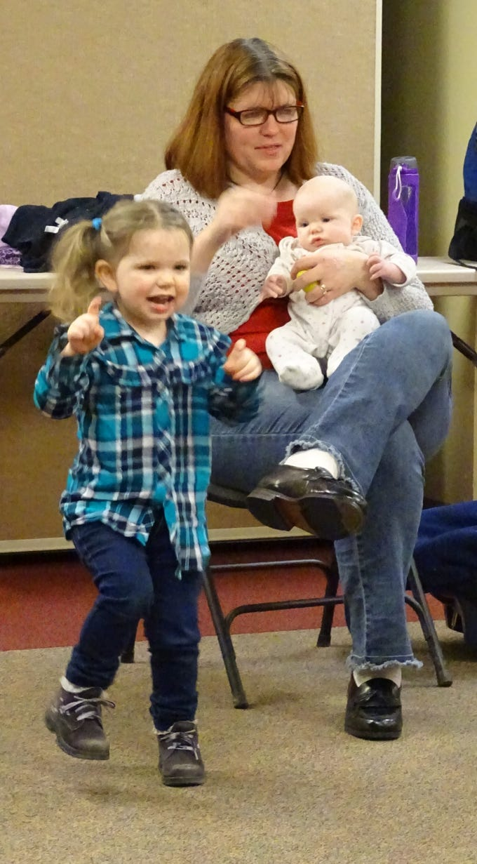 Hannah Wilson, 3, dances while her mother, Laura, holds 3-month-old Marcus  during Music, Movement and More at the Bucyrus Public Library on Monday.