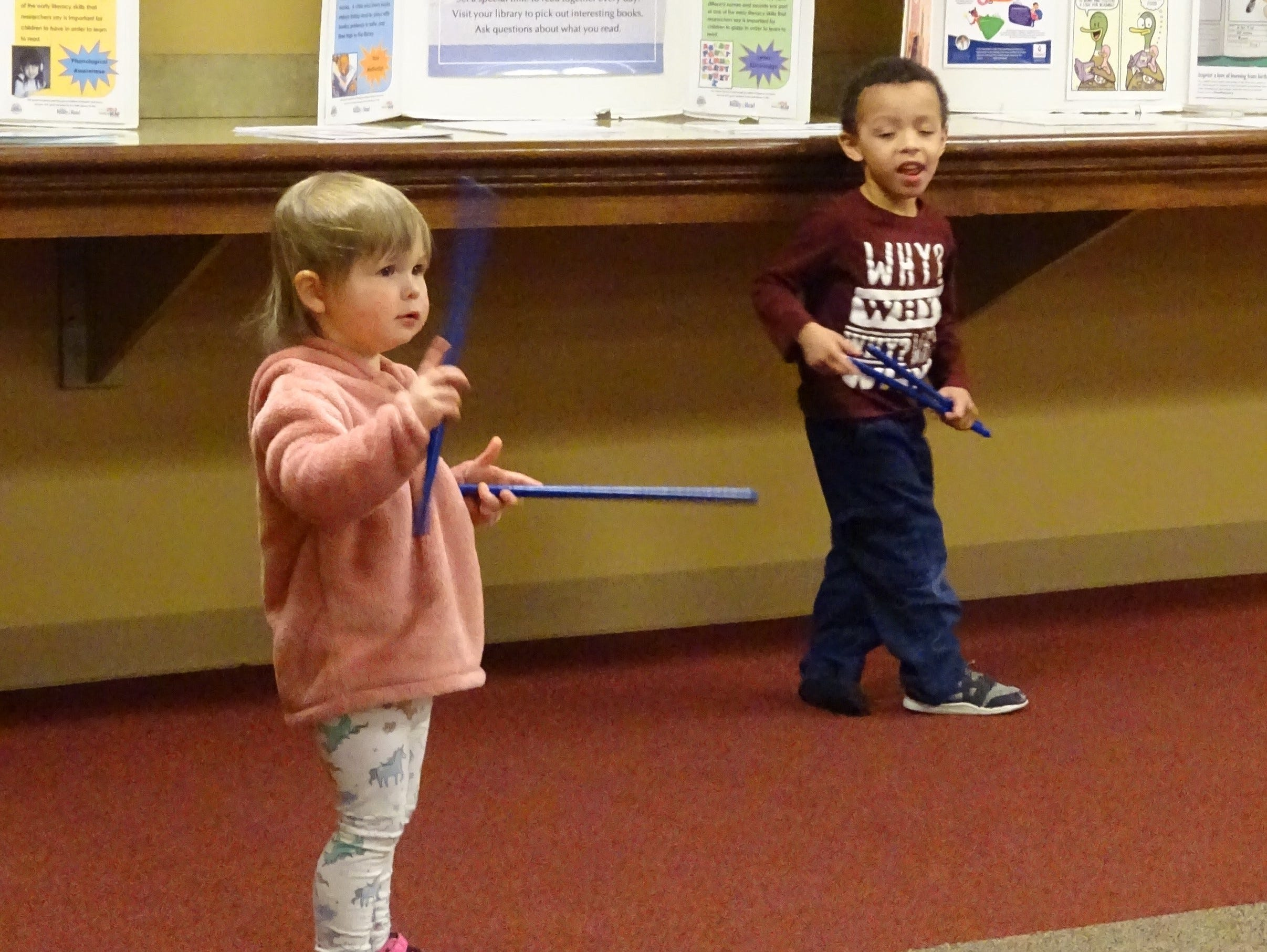 Lexi Bowser, 2, left, waves sticks to the music  during Music, Movement and More at the Bucyrus Public Library on Monday.