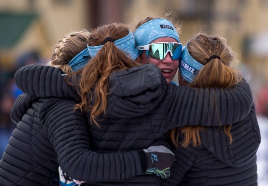 Mount Mansfield's Rose Clayton, center, is hugged by teammates at the finish line after skiing the winning leg of the Cougars' title-clinching relay at the Vermont high school Nordic ski championships on Monday in Ripton.