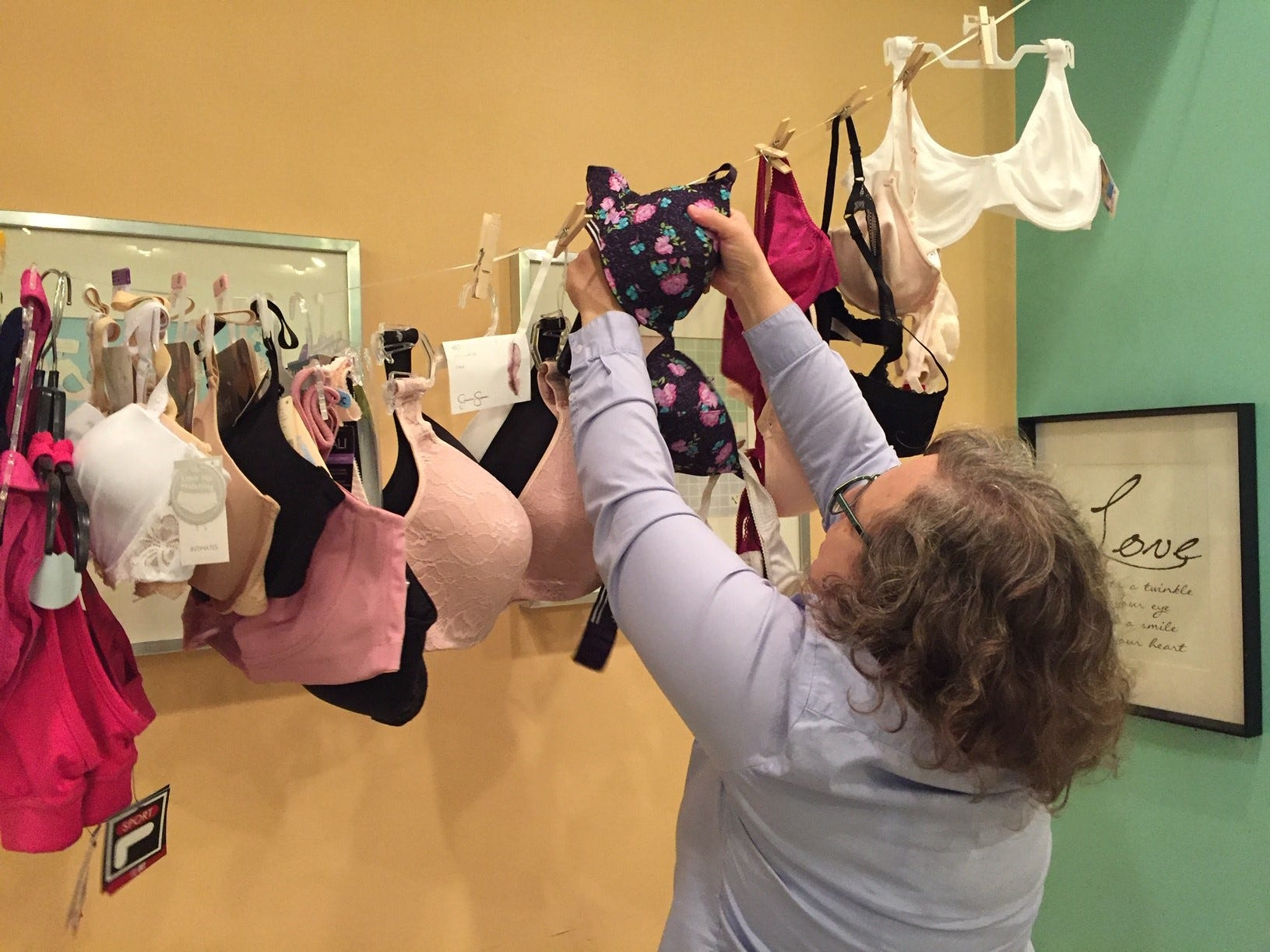 Bras donated at the Galentine's Celebration at the Pop Shop in Collingswood are strung up by Courier-Post reporter Kim Mulford. Bras are donated to Distributing Dignity for women in need.