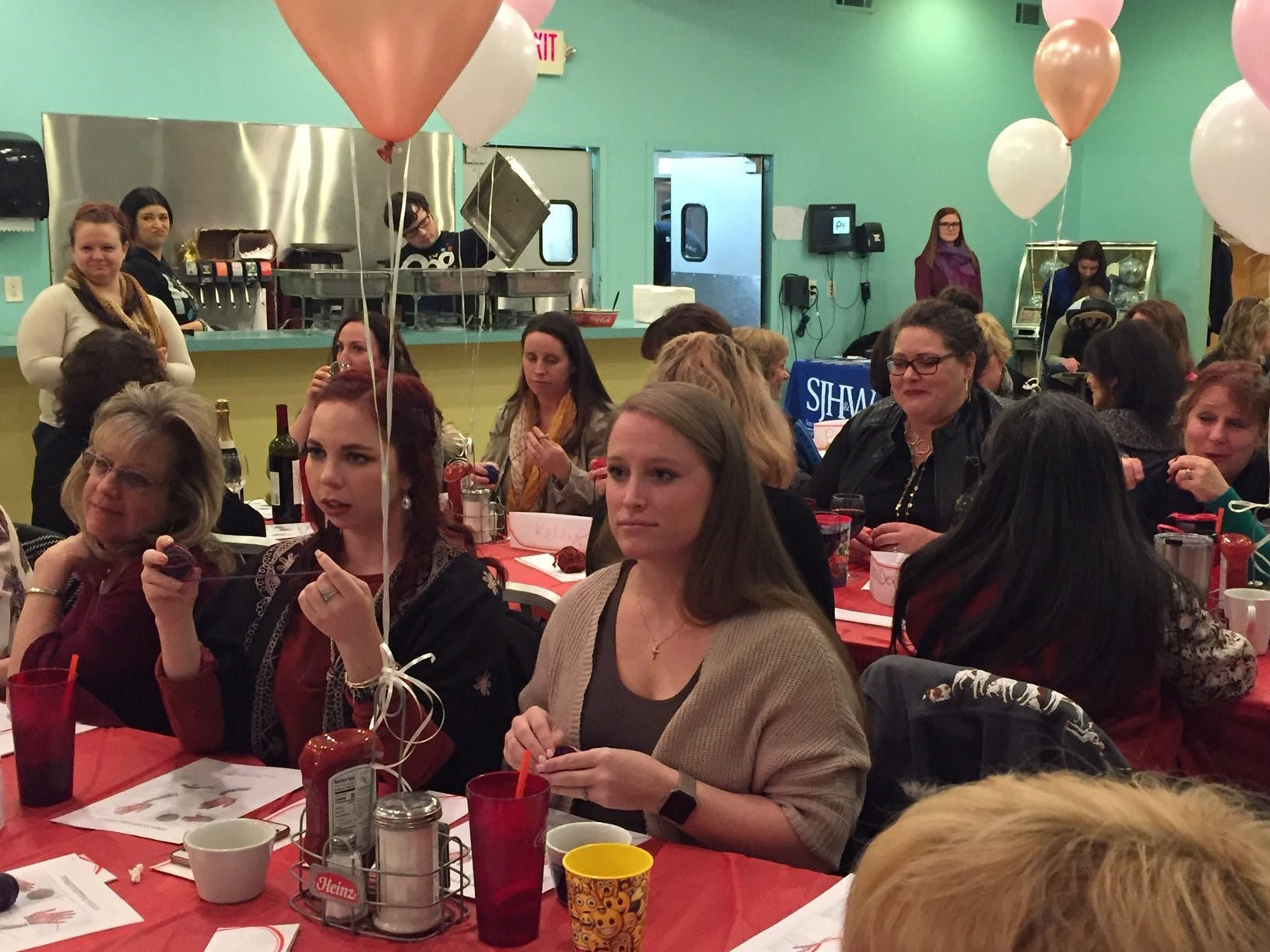 Guests experiment with hand knitting for stress relief at The Pop Shop in Collingswood during the Galentine's Celebration.