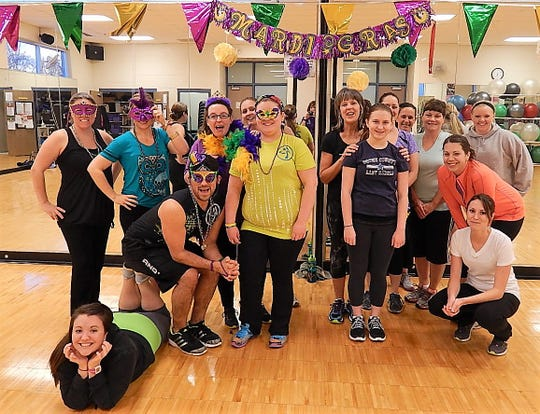 A group poses at a previous Mardi Gras-themed fitness event.