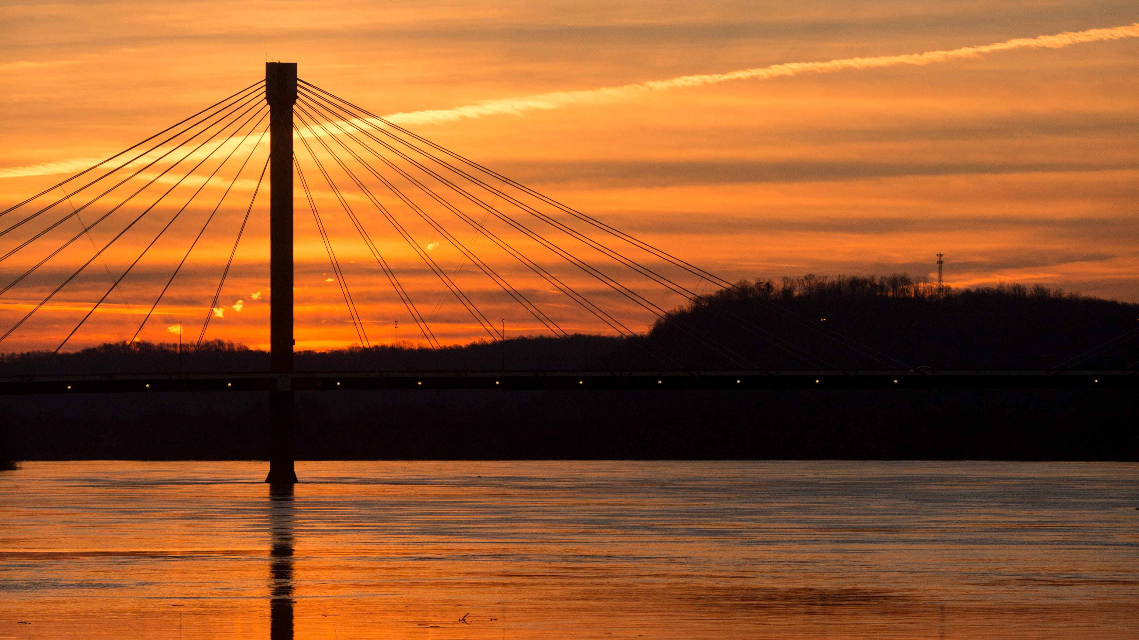 A sunrise silhouettes the US Grant Bridge in Portsmouth, Ohio. Portsmouth sits at the intersection of the Ohio River (pictured) and the Scioto River. Michael Mearan, prominent Portsmouth attorney, is part of an 80-page affidavit created by the Drug Enforcement Administration in 2015 to obtain permission to wiretap several phone, including Mearan's. It alleges he is part of a sex trafficking network.