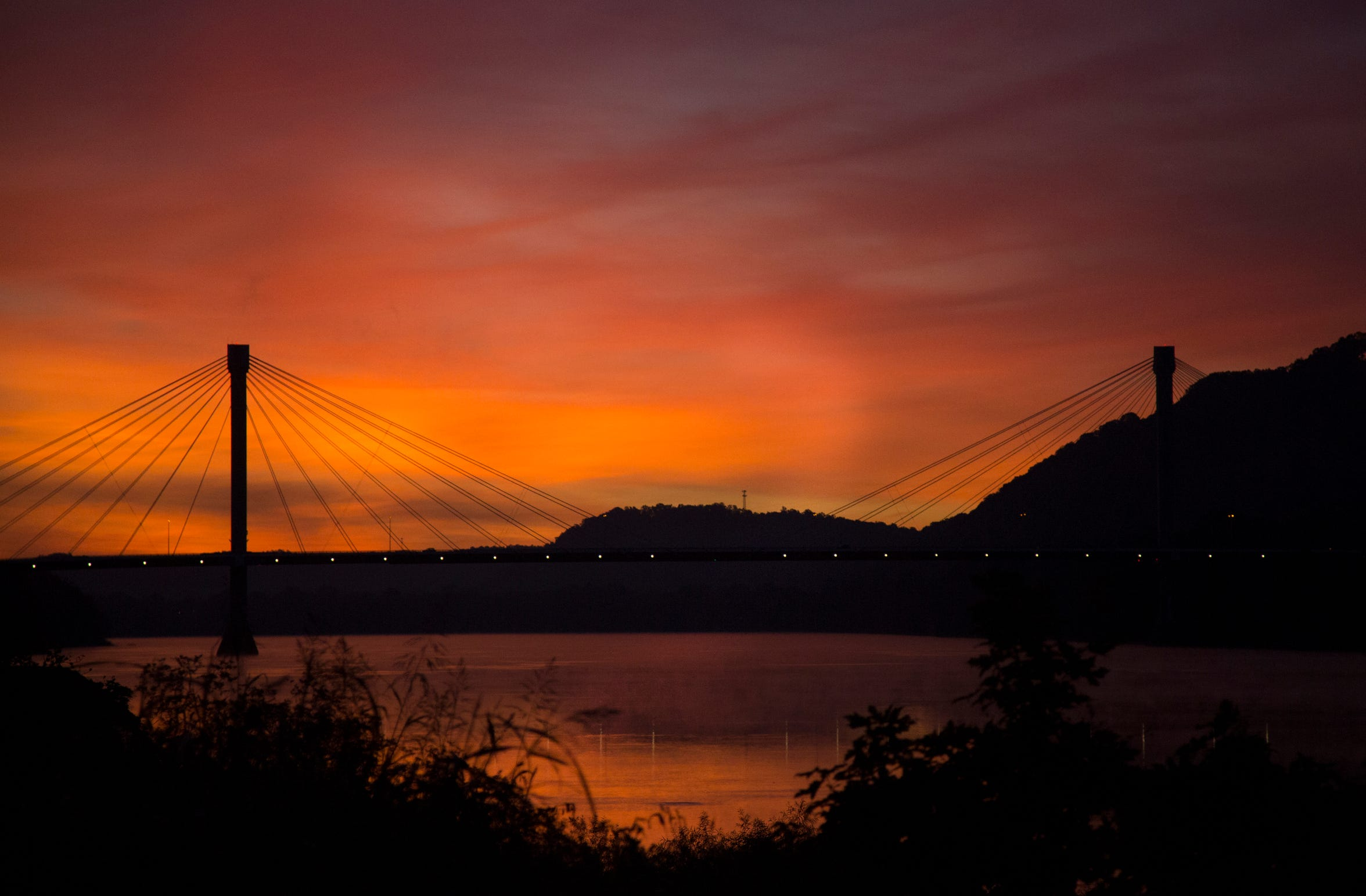 A sunrise silhouettes the US Grant Bridge in Portsmouth, Ohio. Portsmouth sits at the intersection of the Ohio River (pictured) and the Scioto River.