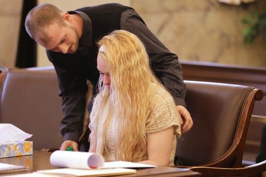 Samantha Davis, seated, is being consoled by a family member Friday, March 1, 2019 during her trial in Hamilton County Common Pleas Court.