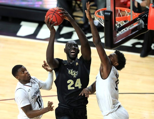 UCF center Tacko Fall (24) drives to the basket against Cincinnati center Nysier Brooks, right, and forward Trevon Scott, left, in the second half on Feb. 21.  Aaron Doster/USA TODAY Sports Feb 21, 2019; Cincinnati, OH, USA; UCF Knights center Tacko Fall (24) drives to the basket against Cincinnati Bearcats center Nysier Brooks (33) and forward Trevon Scott (13) in the second half at Fifth Third Arena. Mandatory Credit: Aaron Doster-USA TODAY Sports