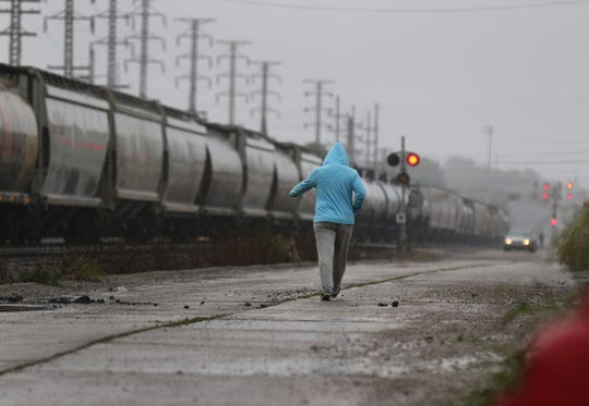 A young woman walks along side a train on a rainy afternoon in Portsmouth, Ohio. Trains are a constant in the small rural town of about 20,000.