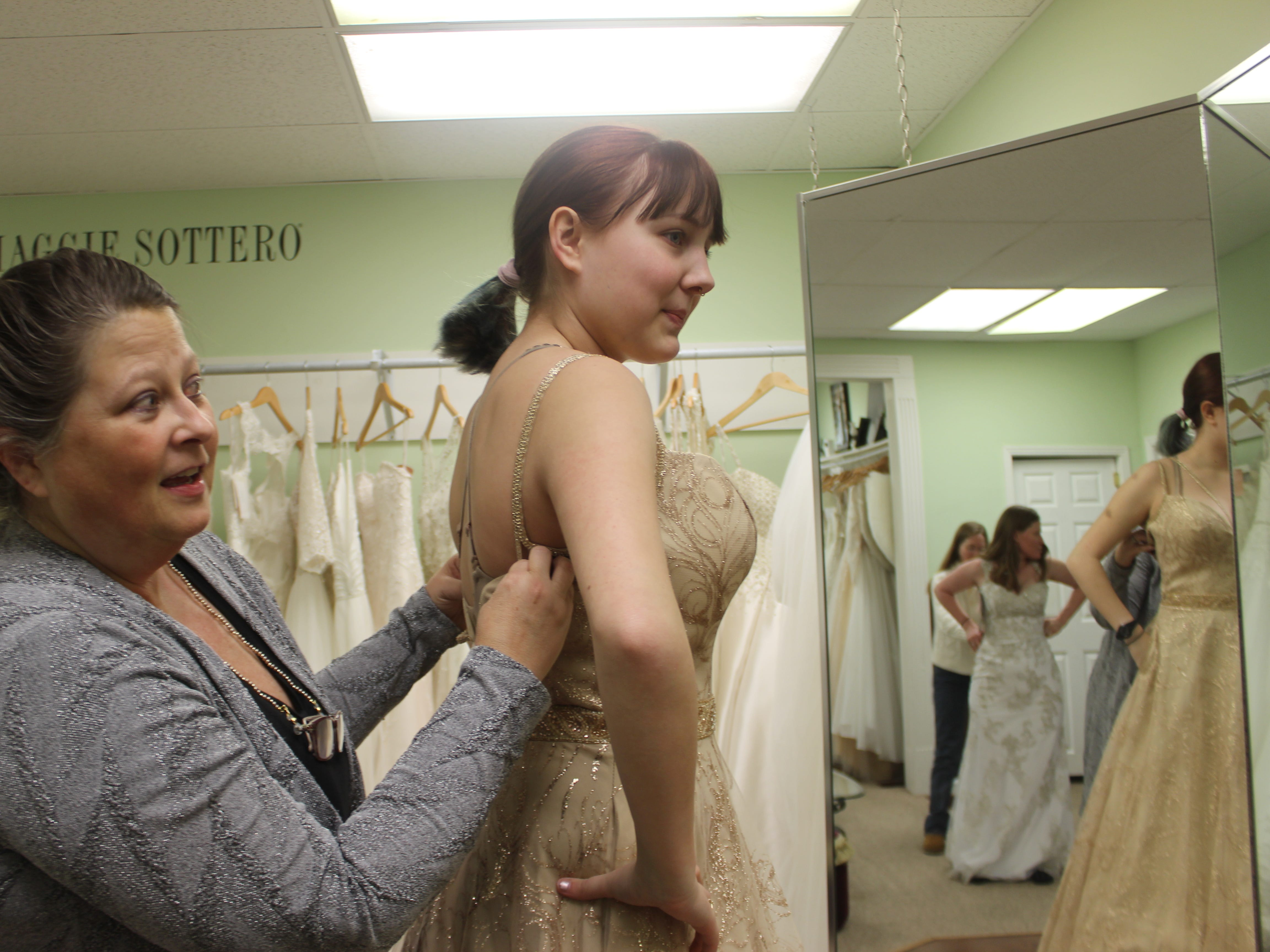 Mara Ferguson tries on a gold ball gown with strappy details at Wedding Belles in Clarksville, as owner Lisa Forest assists.