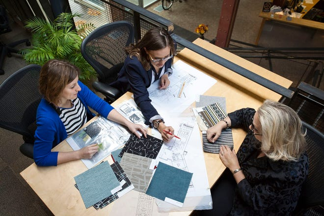 Leann Pederson, Collin R. Barnes and Catherine Neumann (from left), registered interior designers, work on a project at RDG Planning & Design in October 2014.