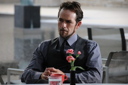 Luke Perry, in-character as The Thief in the movie Same Steele and the Junior Detective Agency, sits in the courtyard at the Des Moines Art Center in June 2009.