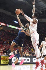 Zavier Simpson takes a hook shot over Maryland's Bruno Fernando in the first half at the XFinity Center on March 3, 2019, in College Park, Maryland.