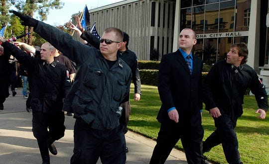 In this Saturday, Nov. 5, 2011 file photo, Jeff Schoep, second right in business suit, commander of the National Socialist Movement, leave under police protection after a rally against illegal immigration in Pomona, Calif. One of the largest and oldest neo-Nazi groups in the U.S. appears to have an unlikely new leader: James Stern, a black activist who has vowed to dismantle it. Michigan corporate records indicate Stern replaced Jeff Schoep as the Detroit-based group's leader in January. Stern and Schoep didn't respond to requests for comment.