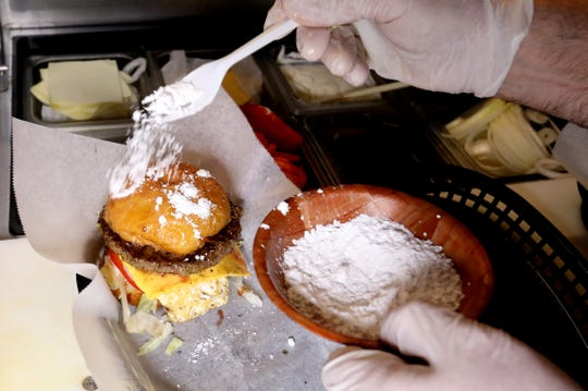 John Gjuncaj, a cook at Motor City Sports Bar and Grill in downtown Hamtramck, Michigan, adds a finishing touch of powdered sugar to a made-to-order Paczki burgers on Saturday, March 2, 2019.The Paczki burger created by Nik Nuculaj, owner of Many people crowded the bar with some trying the burger after the Paczki 5k run that happened earlier on Saturday morning.