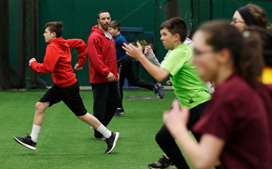 In this Wednesday, Feb. 27, 2019, photo, Anthony Sarigianopoulos trains children and young adults at the Sluggers of Ohio gym in Youngstown, Ohio. Sarigianopoulos has put in 25 years at GM's plant in Lordstown, Ohio, where the last Chevrolet Cruze will roll off the assembly line soon. Sarigianopoulos, who checks and fixes cars at the end of the line, knows he is fortunate to have a shot at a job even if it's somewhere else, unlike most of the 8,000 white-collar employees GM is laying off and those who are losing jobs at the automaker's nearby parts suppliers.