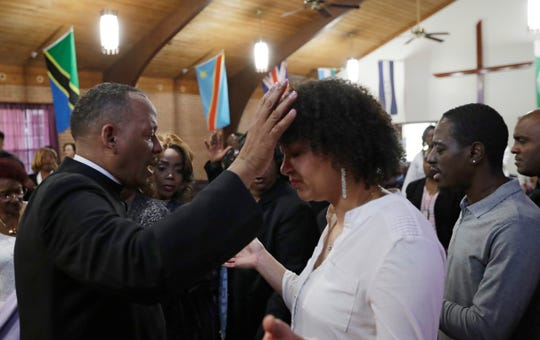 """Pastor Melvin Trent, left, prays with a parishioner during a service at the New Beginnings Outreach Ministries, Sunday, March 3, 2019, in Youngstown, Ohio. Trent stood before about 150 members of his church in early February and told them he was leaving. His wife, an engineer with GM, was being sent to its SUV plant in Arlington, Texas. Trent, 55, who retired after 35 years with the automaker, said it was a """"no-brainer"""" to accept the relocation but not an easy decision."""