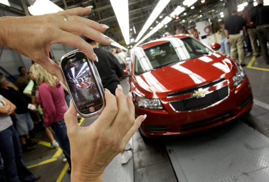 FILE - In this Sept. 8, 2010, file photo, an auto worker takes a picture of the first Chevrolet Cruze compact sedan to come off the assembly line at a ceremony inside the GM factory in Lordstown, Ohio. GM employees in Lordstown and other factories in Michigan and Maryland that are targeted to close within a year say moving will force them to leave behind relatives, even their children, in some cases.