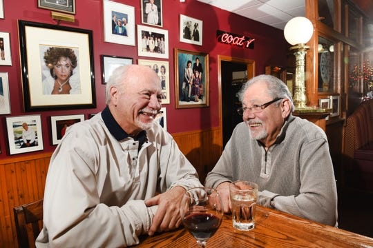 John Ginopolis, right, co-owner of  Ginopolis'  Bar-B-Q Smokehouse in Farmington Hills, chats talks with long-time customer Bill Phillips at the spot in the bar that the regulars call Amen Corner.