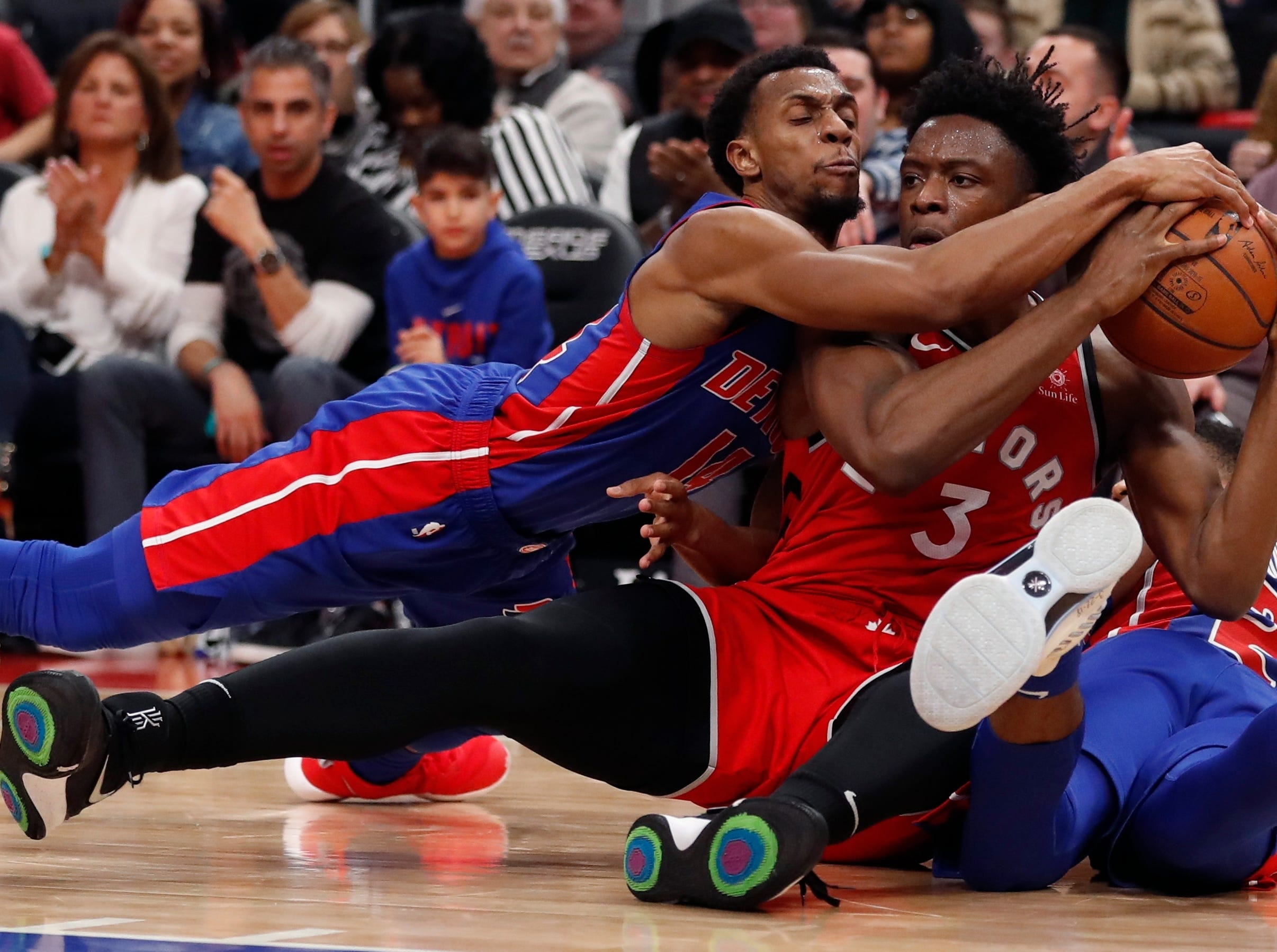 Detroit Pistons guard Ish Smith, left, and Toronto Raptors forward OG Anunoby (3) chase the loose ball during the second half.