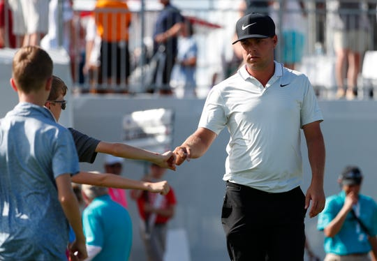 Keith Mitchell, right, fist-bumps a group of children as he heads to the 10th tee during the final round of the Honda Classic golf tournament, Sunday, March 3, 2019, in Palm Beach Gardens, Fla.