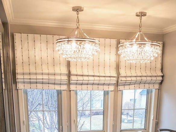 The newly remodeled master bath in Patricia Warner's home is filled with deluxe touches like the chandeliers displayed above a soaking tub and a spacious shower surrounded by glass. Tile floors that look like wood join custom Roman shades on the windows.