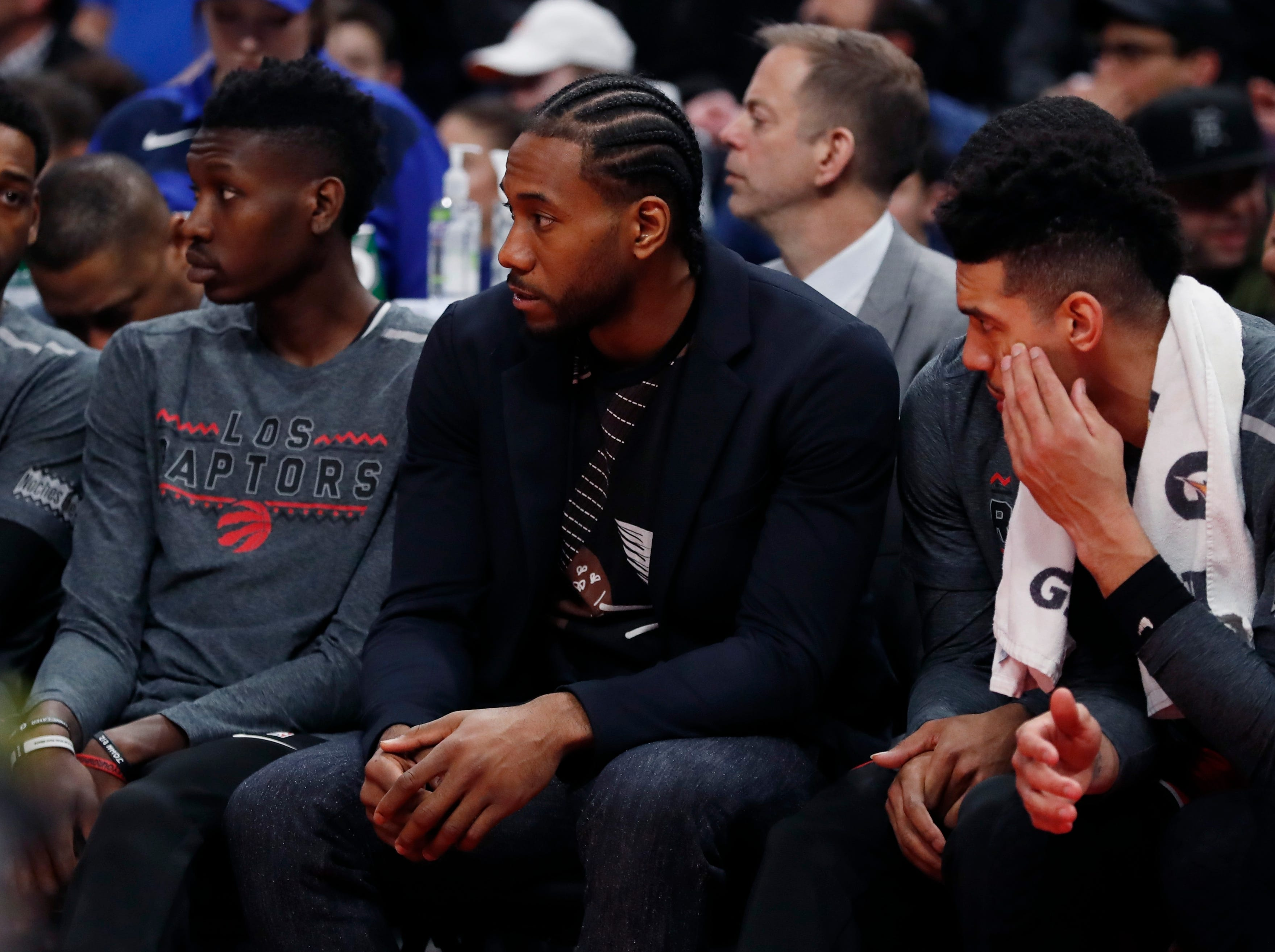 Toronto Raptors forward Kawhi Leonard, center, sits on the bench during the second half.