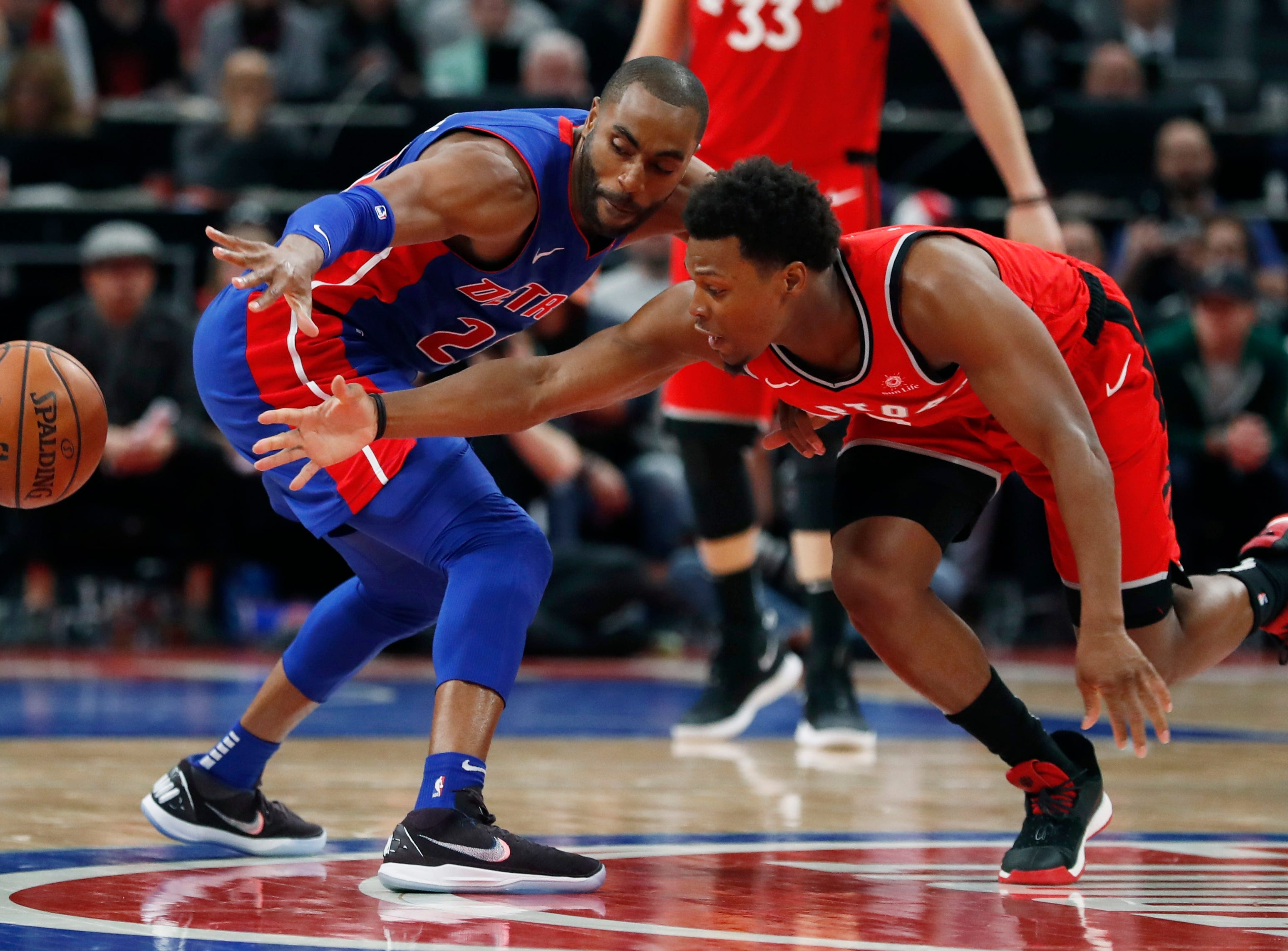 Detroit Pistons guard Wayne Ellington, left, and Toronto Raptors guard Kyle Lowry (7) reach for the loose ball during the second half.