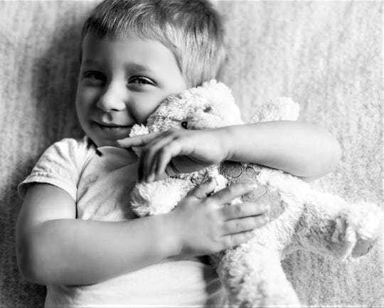 Jack Hastrich hugs a teddy bear that was made by Molly's Bears, an organization that creates weighted teddy bears for families coping with infant loss, in memory of his twin brother Mitchell.