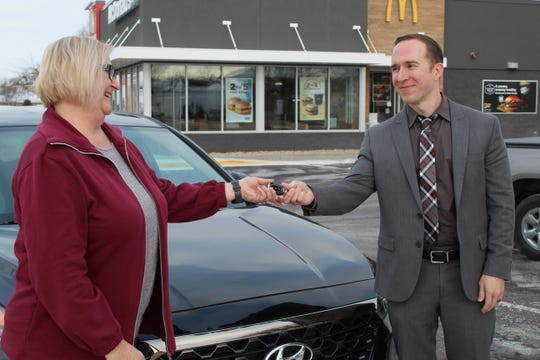 Clyde McDonald's store owner Luke Humbard, right, hands keys to a 2019 Hyundai Santa Fe to Teresa Slosser, of Clyde.