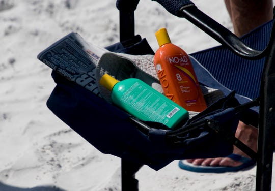 Sunscreen sits on Fort Myers Beach on Feb. 4, 2019. Some say that certain sunscreens should be banned because the ingredients are bad for the environment.
