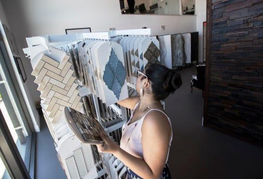 Bailey Arias arranges backsplash tile samples at the new Armex Design Studio.