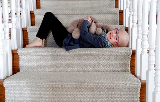 Lily Wertel, 6, lays on the staircase of her family's home in Wrightstown, Wis. with her stuffed elephant, Toby. A benefit for Lily, who has cancer, is scheduled for May 19, 2019, at the Riverside Ballroom in Green Bay, Wis.