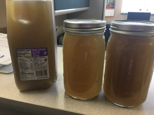 These jars contain brown water taken from a tap in Kewaunee County that researchers tied to the spreading of manure on a nearby field. The soil from the field and water from the home shared the same signatures for fecal contaminants.